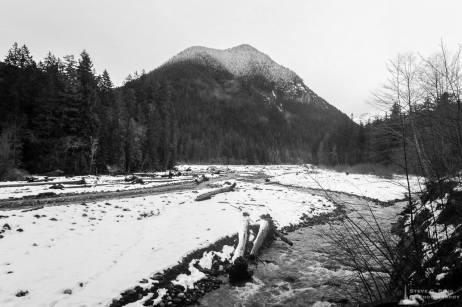 A black and white landscape photograph of the Carbon River in Mount Rainier National Park, Washington after a Winter snowfall.