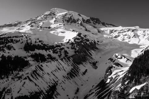 A black and white landscape photograph of Mount Rainier with the last light of a sunny Spring day shining on it as viewed from the Nisqually Vista in the Paradise area of Mount Rainier National Park, Washington.