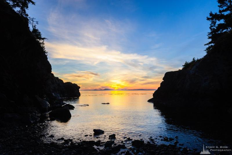 A landscape photograph of the setting August sun on a small inlet at Lighthouse Point at Deception Pass State Park, Washington.