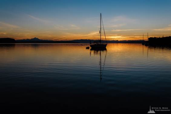 A landscape photograph of the summer sunrise over Penn Cove on Whidbey Island near Coupeville, Washington.