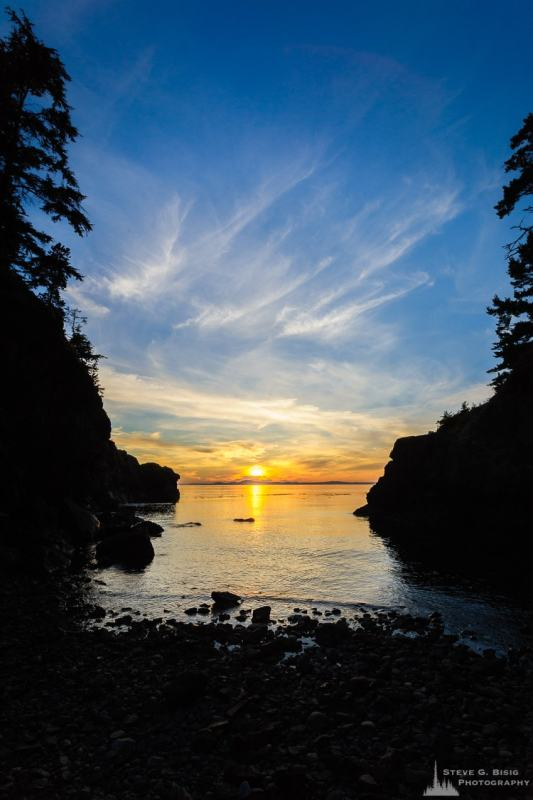A landscape photograph of the August sunset on a small inlet at Lighthouse Point at Deception Pass State Park, Washington.