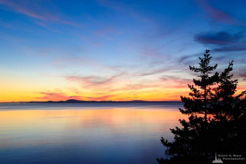 A landscape photograph of the setting sun over Northwest Pass at Deception Pass State Park, Washington.
