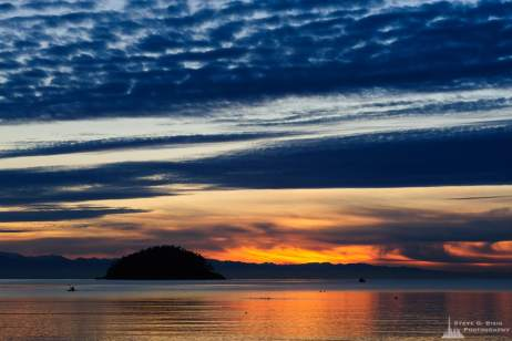 A landscape photograph of Deception Island and the calm waters of Bowman Bay during an early winter sunset at Deception Pass State Park, Washington.