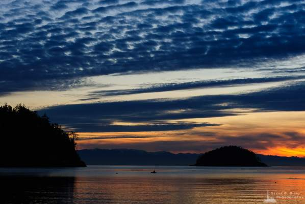 A landscape photograph of a lone kayaker enjoing the calm waters of Bowman Bay on a January evening at Deception Pass State Park, Washington.