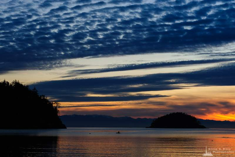 A Pacific Northwest landscape photograph of a lone kayaker enjoying the calm waters of Bowman Bay on a January evening at Deception Pass State Park, Washington.