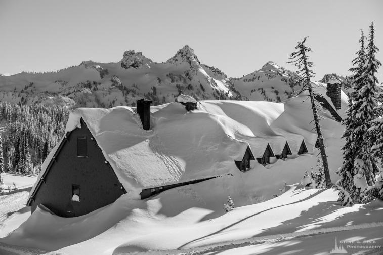 A black and white photograph of the historic Paradise Inn under a heavy blanket of snow as captured on a sunny winter day in the Paradise area of Mount Rainier National Park, Washington.