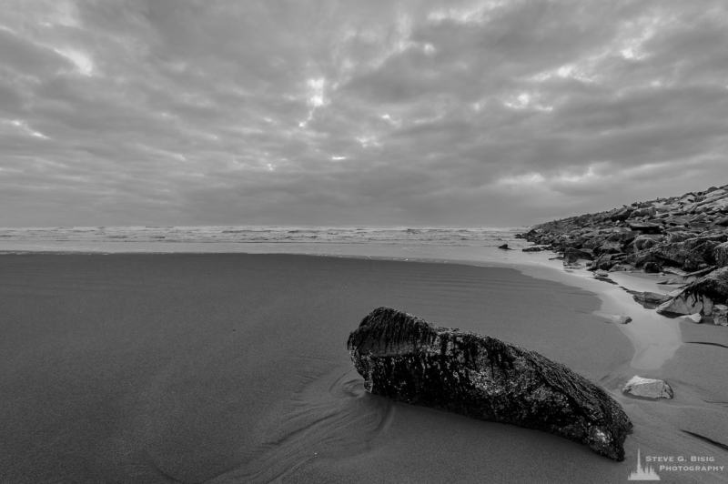 A black and white landscape photograph of the Pacific Ocean beach along the South Jetty of Grays Harbor at Westhaven State Park near Westport, Washington.