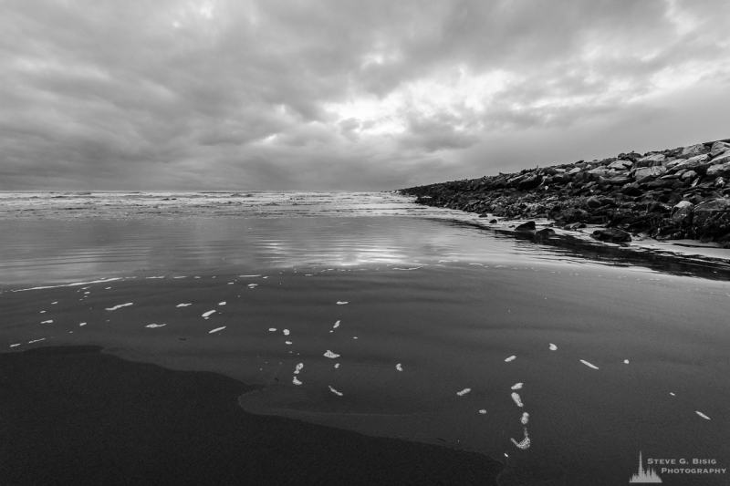 A black and white landscape photograph of the Pacific Ocean surf and beach along the South Jetty of Grays Harbor at Westhaven State Park near Westport, Washington.