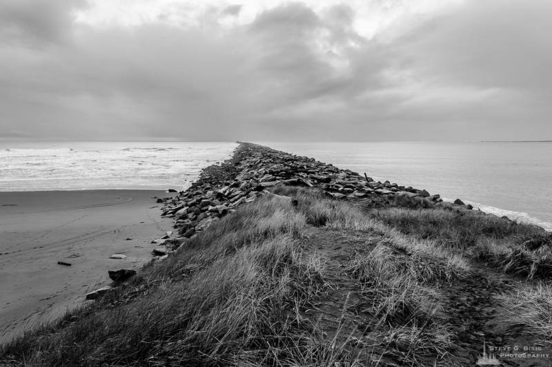A black and white landscape photograph of the South Jetty between the Pacific Ocean and Grays Harbor at Westhaven State Park near Westport, Washington.