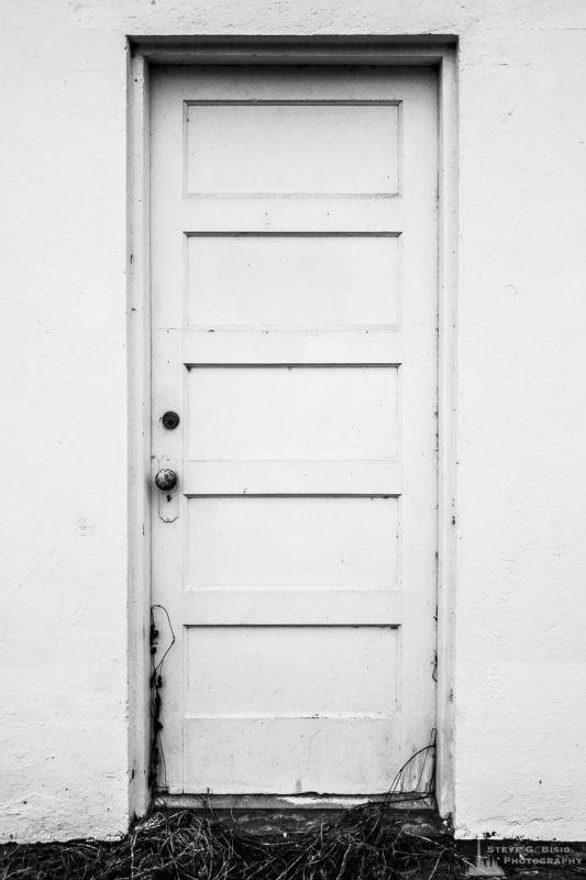 A black and white mobile urban photograph of an old white door on an abandoned building in Oak Harbor, Washington.