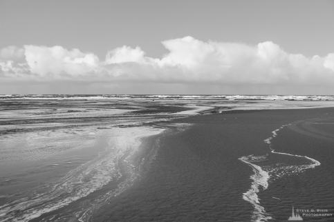 A black and white landscape photograph of the Pacific Ocean along South Beach in Pacific County, Washington.