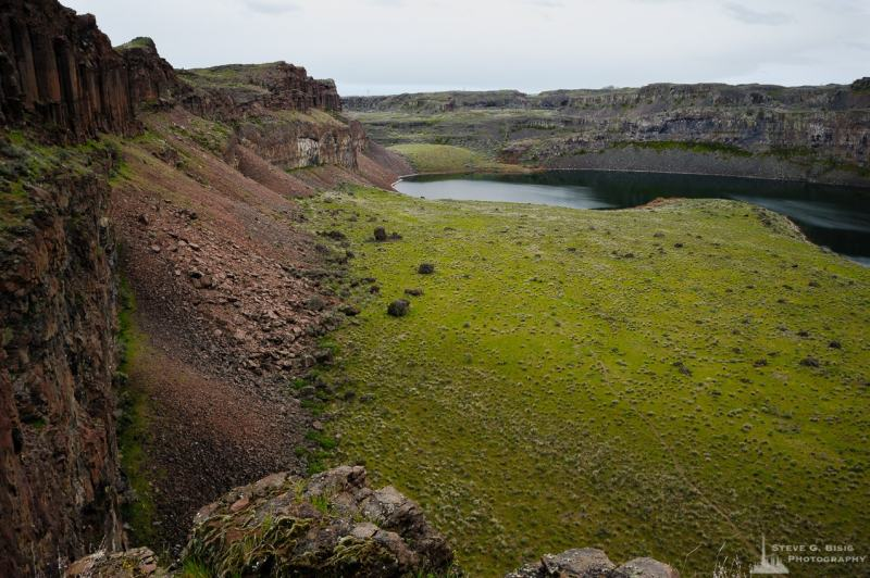 A landscape photograph of Dusty Lake as seen from a saddle between two arms of the Potholes Coulee in the Quincy Lakes Unit of the Columbia Basin Wildlife Area in Grant County, Washington.