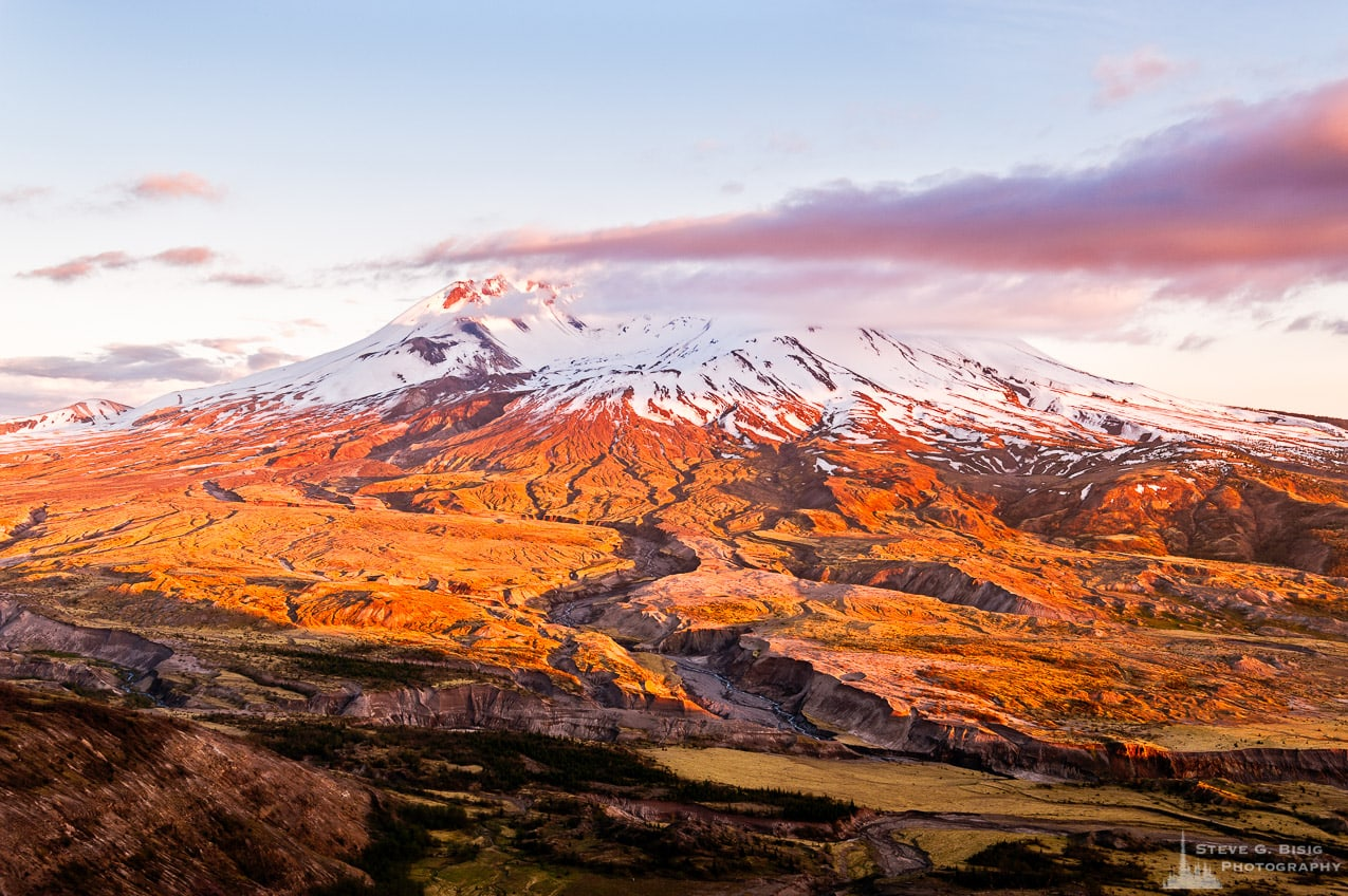 A landscape photograph of Mount Saint Helens shrouded by clouds and the evening glow on the plains below as seen from the Johnston Ridge Observatory, Washington.