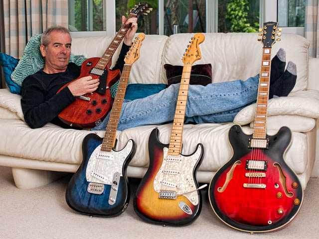 Guitarist Reclining On Sofa Surrounded With Guitar Collection