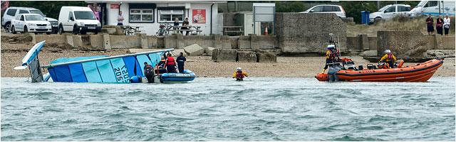 Rnli Crew In Water With Capsized Catamaran Boat