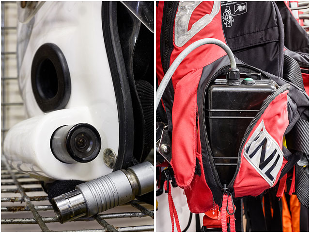 White RNLI Helmet Radio and Camera with Battery Pack Hanging in Red Life Preserver