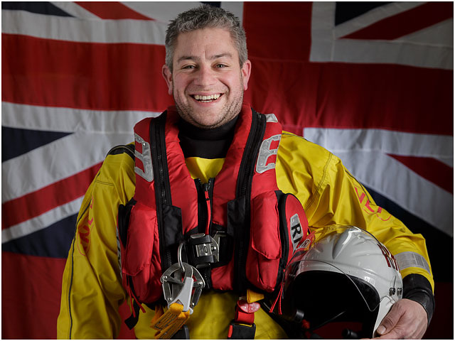 Head and Shoulders Portrait of RNLI Crew Volunteer with White Ensign Flag in Background