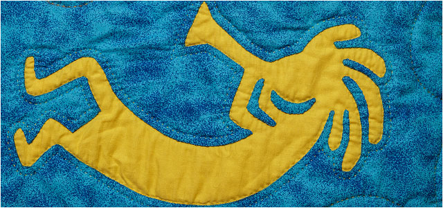 yellow quilted kokopelli figure playing musical instrument on a blue background