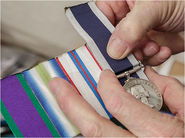 Medal mounter estimating the required length of a ribbon