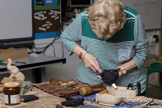 female woodcarver carving a wooden bowl