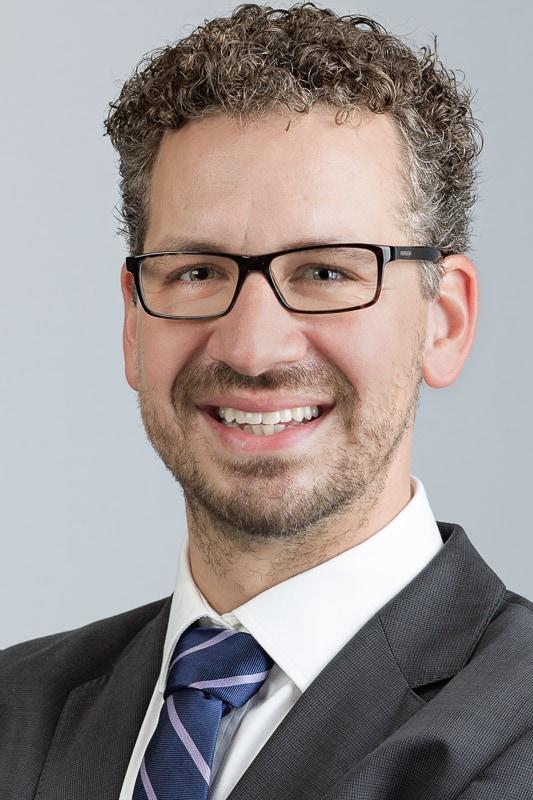 formal businessman headshot against a light grey background