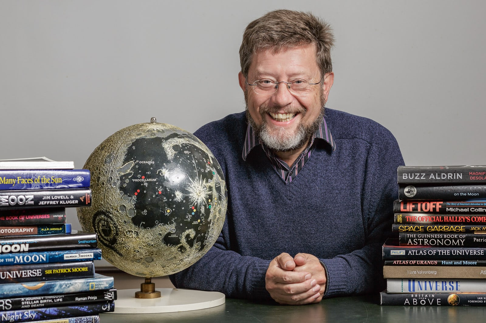 Informal portrait of a head astrologer sat a desk with a globe and books