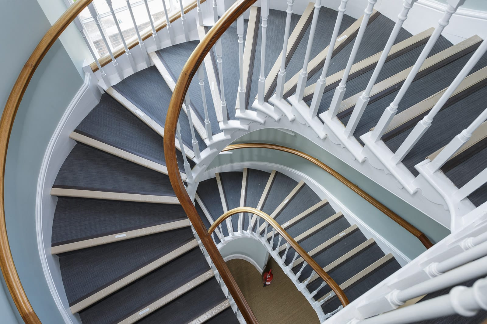 Looking down a museum stairwell with white woodwork and grey blue stair treads