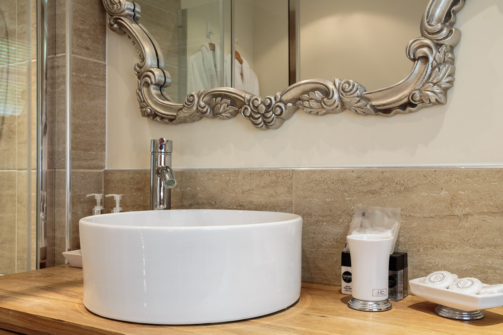 White counter-top bathroom basin with feature ornate mirror