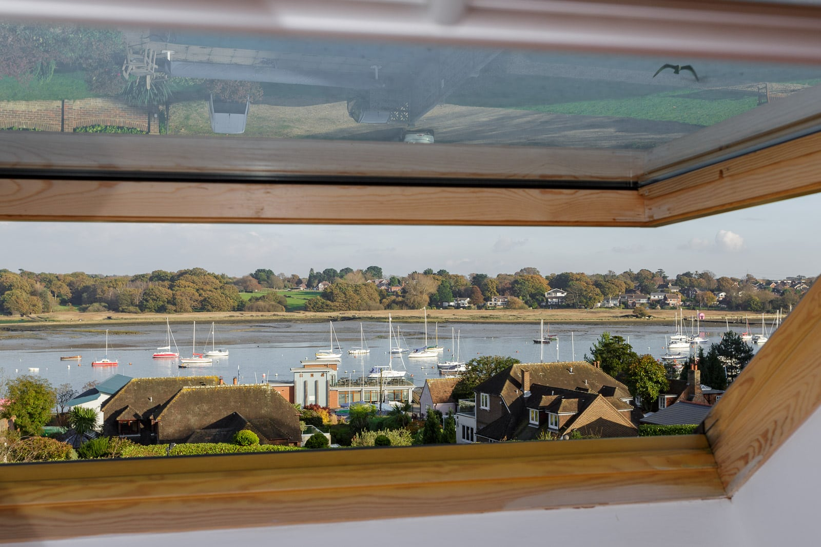 View from a velux roof window featuring a scene across a river with boats