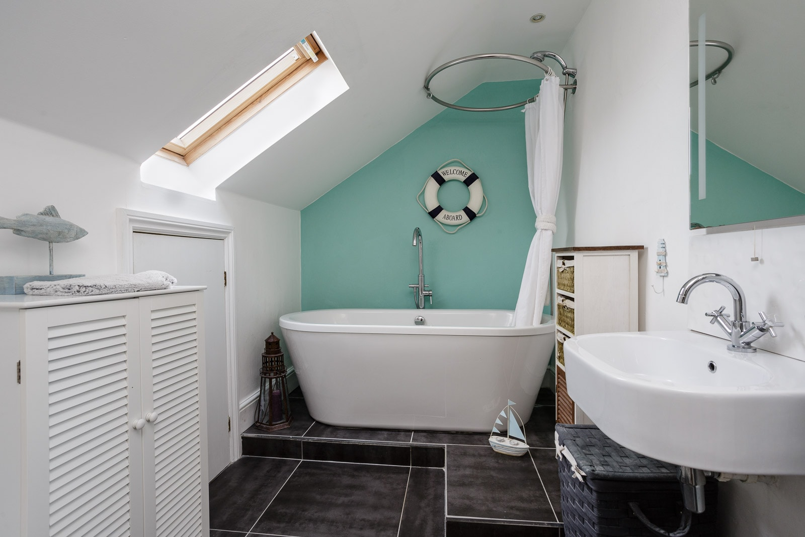 Bathroom with white freestanding roll top bath set in a nautical theme