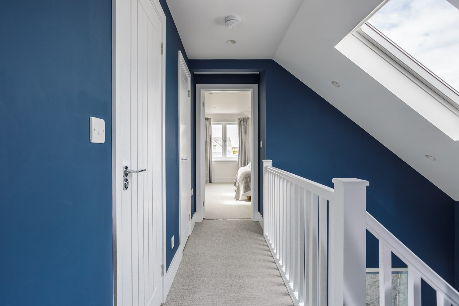 Sleek blue and white colour scheme for modern first floor landing with view into bedroom at the end