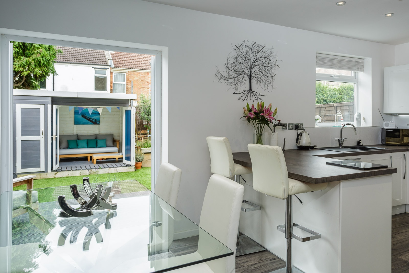 Contemporary glass and stainless steel kitchen with view from patio doors out to garden log cabin
