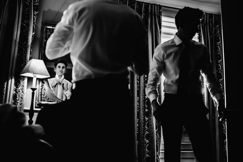 groom and best man getting read at the venue. Photograph by Boconnoc House Wedding Photographer Steven Rooney