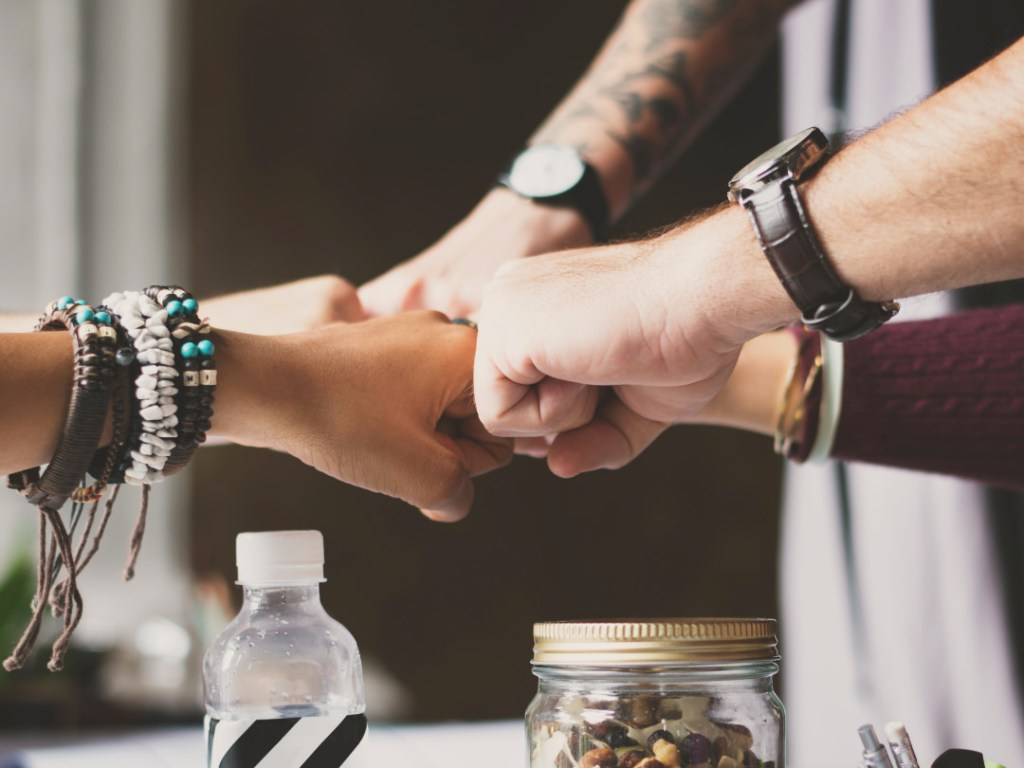 Hands fist-bumping around a table, signifying working together