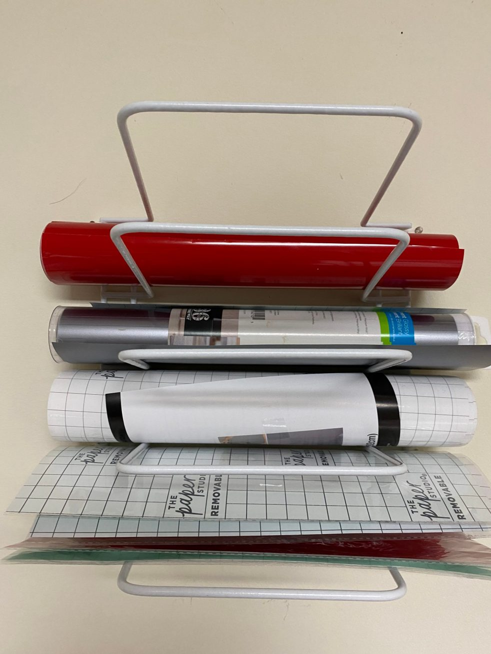 Cheap DIY Wall Vinyl Holder - here is a cheap way to hang up and store your vinyl rolls. #Vinyl #Cricut #DIY
