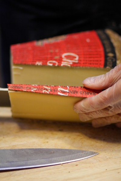 Cutting Comte cheese close up