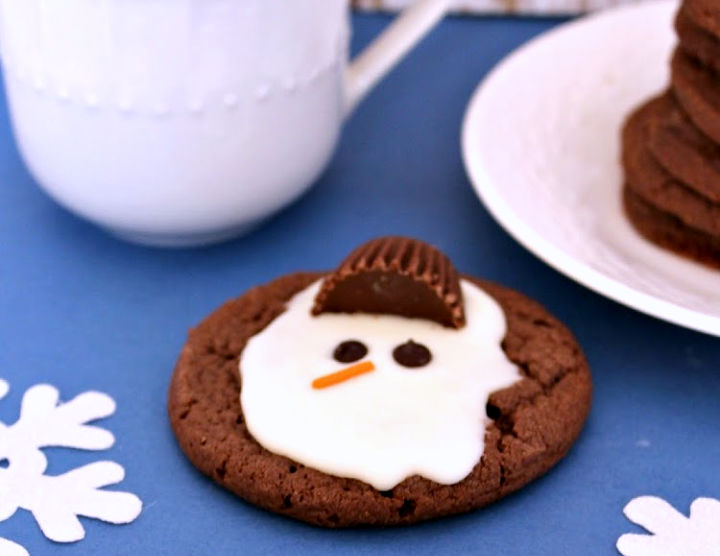 melted snowman cookie sitting beside saucer with mug of milk