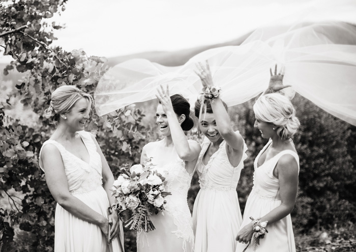 bridal party having some fun with the wedding veil blowing in the wind