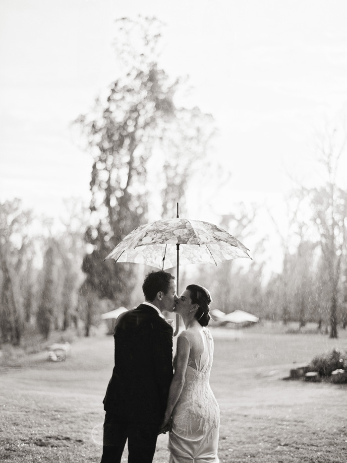 bride and groom in the rain kissing black and white photo