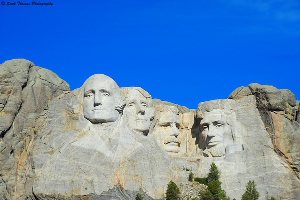 The classic Mount Rushmore photo with perfect blue sky as the background for Presidents George Washington, Thomas Jefferson, Theodore Roosevelt and Abraham Lincoln.