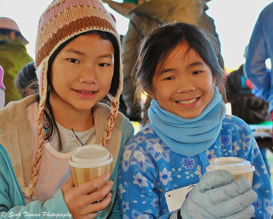 Two of the participants in the Apple Run 1 Mile Fun Run at the Lafayette Apple Festival warm up with hot chocolate as they await the start of their event.