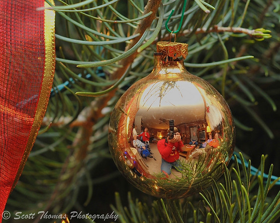 A room full of people enjoying a family Christmas party reflected in an ornament.