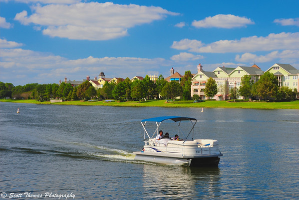 A resort guest pilots a pontoon rental boat past the Saratoga Springs Resort near Downtown Disney in Walt Disney World.