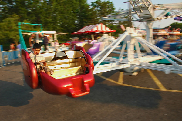 A little boy is learning about centrifugal force first hand while riding a fast moving carnival ride in upstate New York.