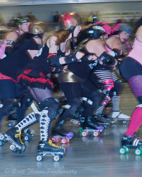 A jammer, the skater with the star on her helmet, works her way through blockers to score points during a roller derby bout in Rome, New York.