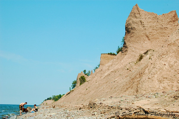 A couple plays with their dog on the rocky shore of Chimney Bluffs State Park near Sodus, New York.