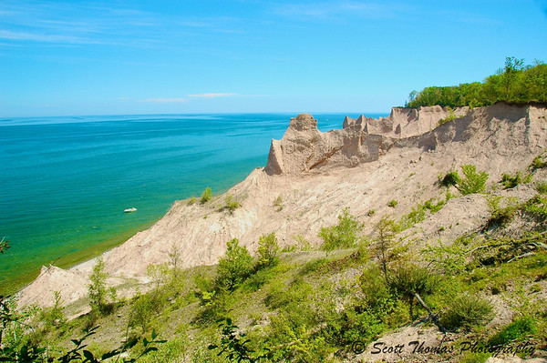 A boat floats off the beach at Chimney Bluffs State Park near Sodus, New York.
