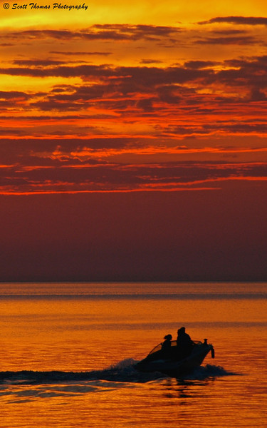 Portrait version of a boat going on an evening cruise on Lake Ontario at sunset.