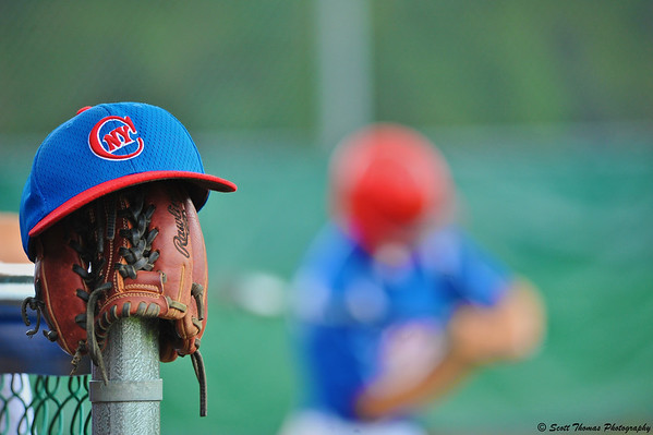 Baseball cap and glove sits on a fence near the dugout as a player swings a bat waiting for his turn at bat.