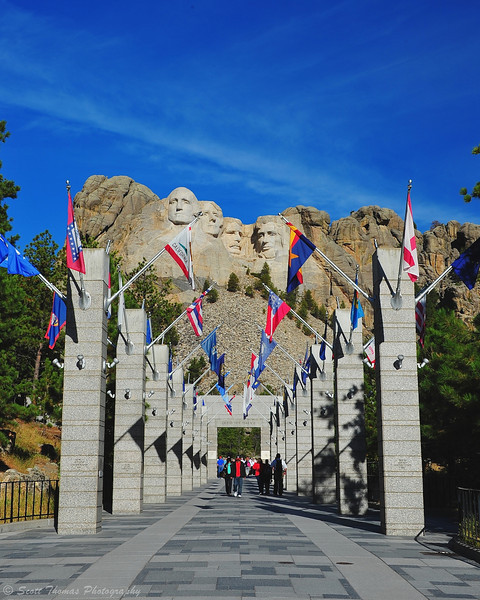 People walk through the Avenue of Flags at the Mount Rushmore National Monument near Keystone, South Dakota.